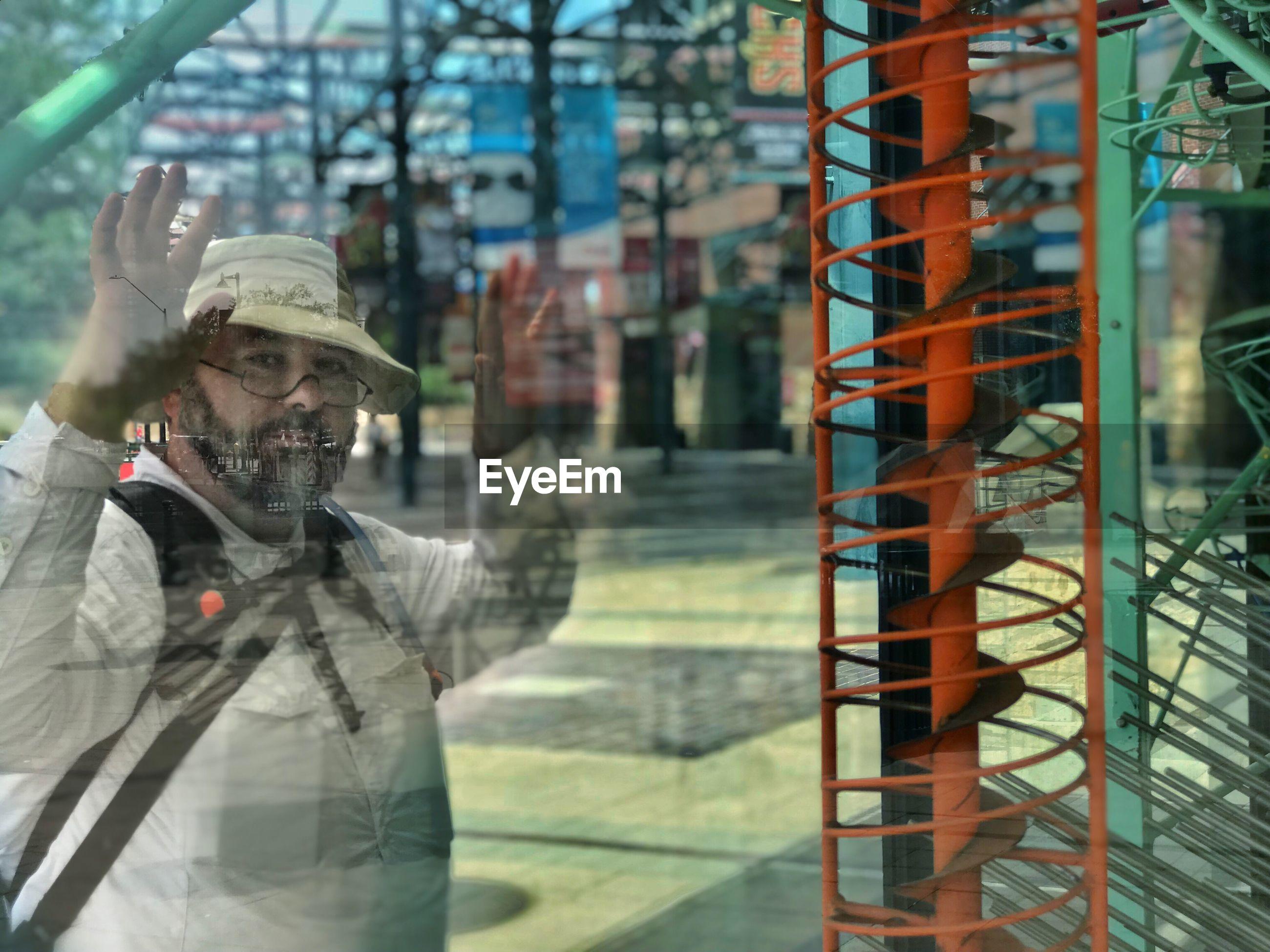 Portrait of man seen through glass window in city