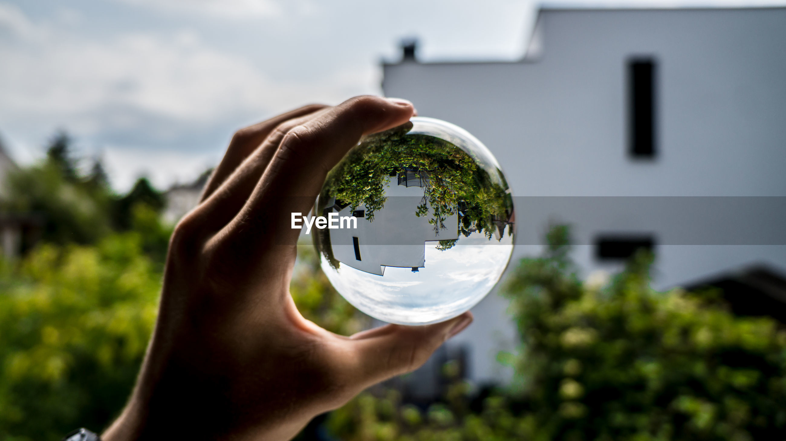 Cropped image of hand holding crystal ball against building