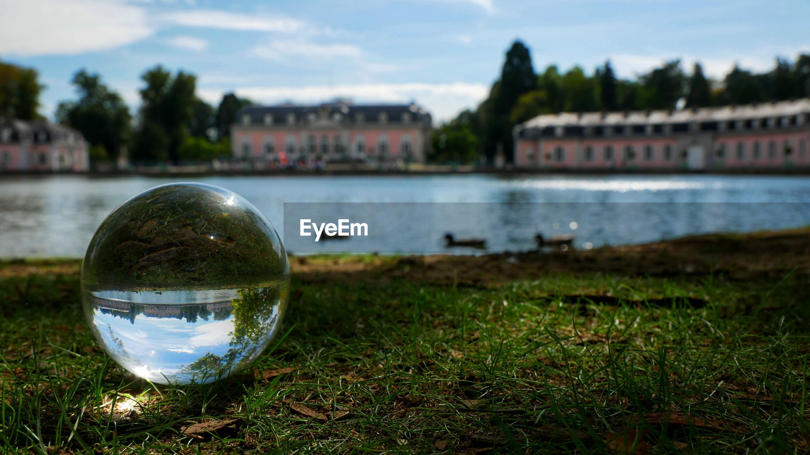 Close-up of crystal ball against lake