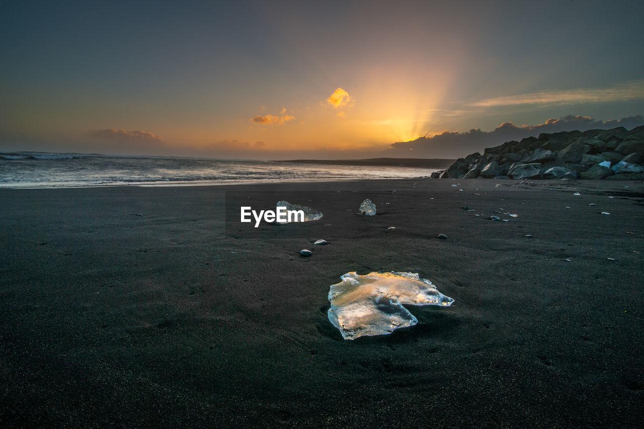 Iceberg On Shore At Beach Against Sky During Sunset