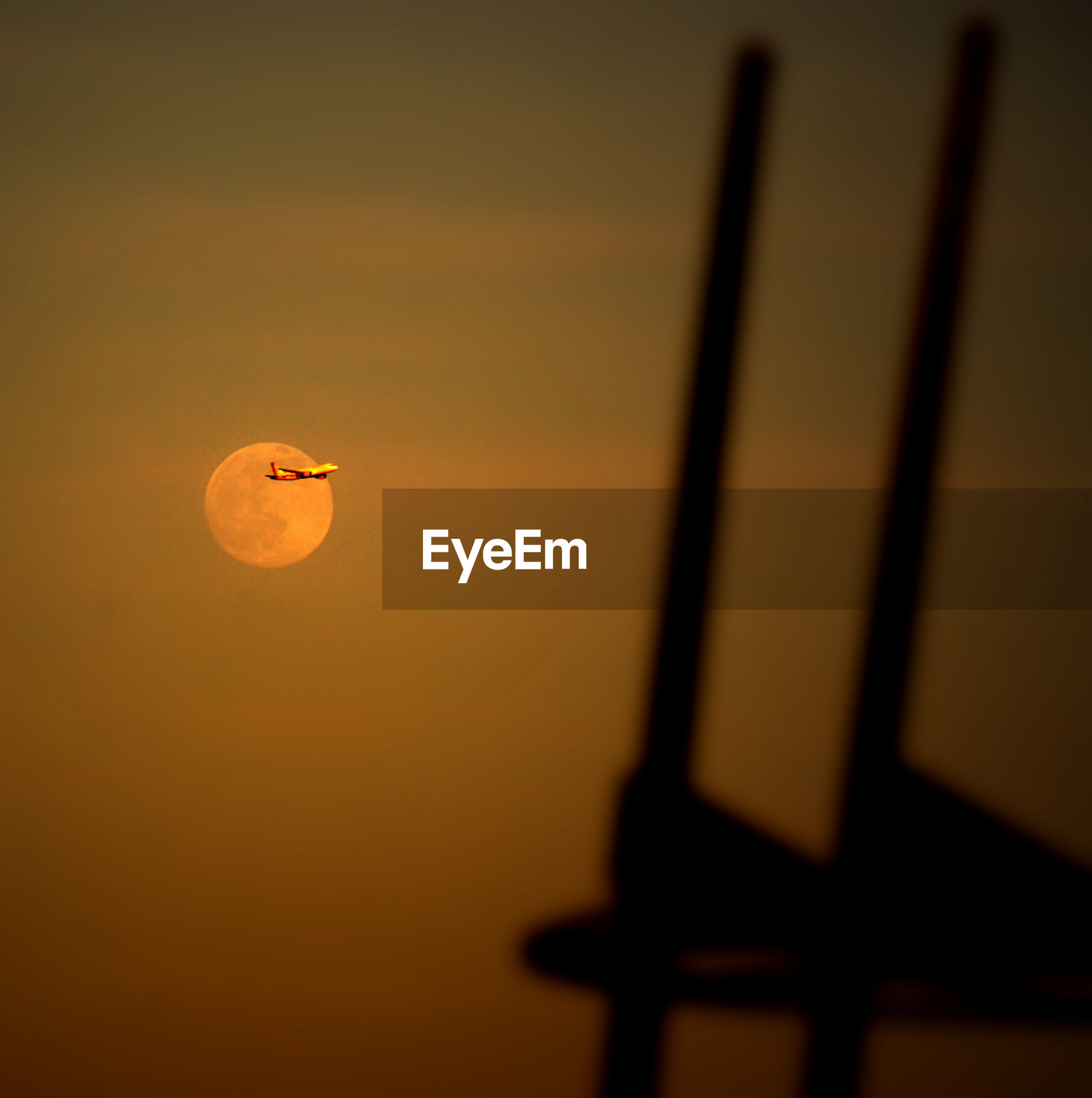 View of airplane against full moon