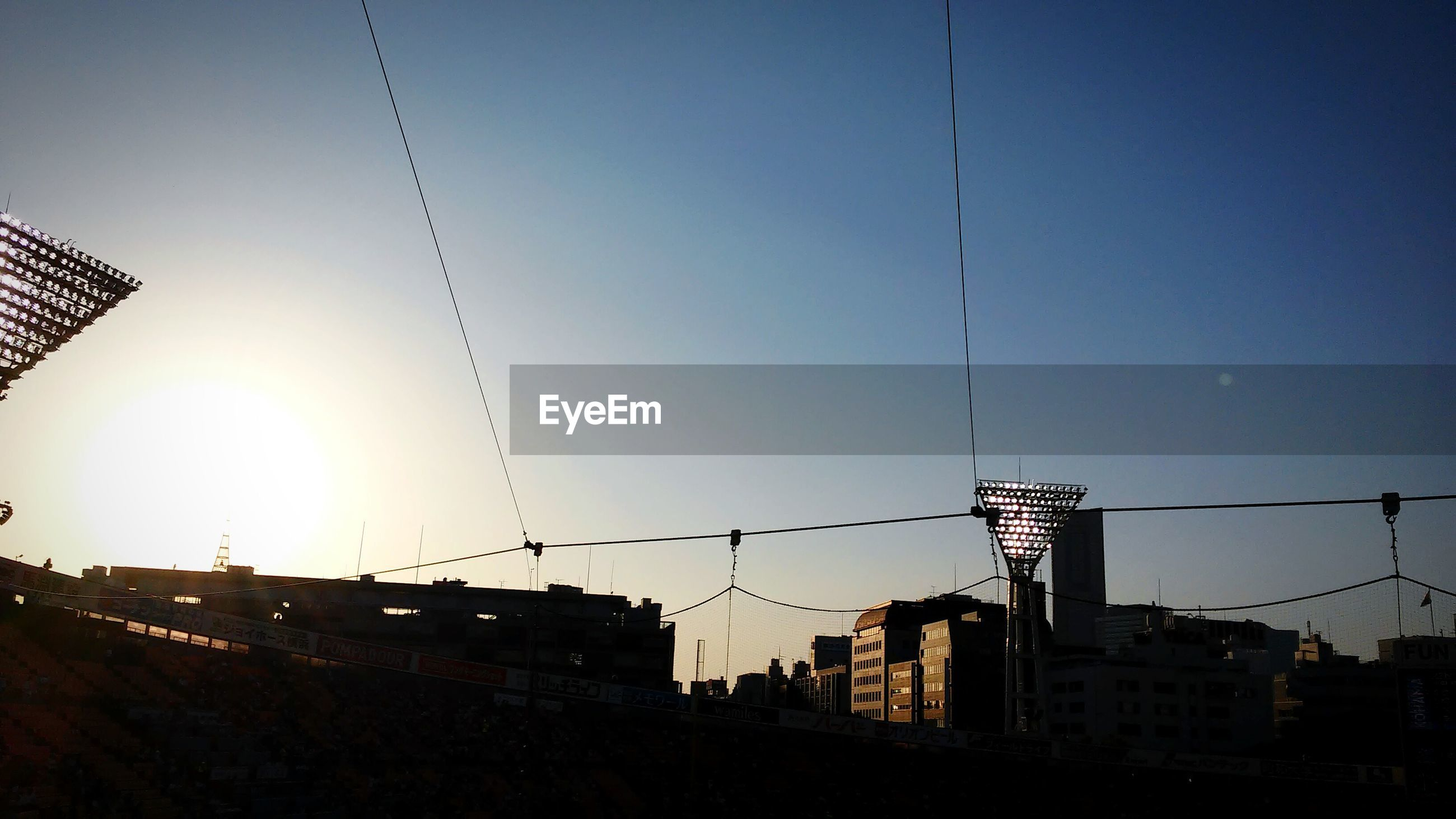 built structure, architecture, building exterior, clear sky, low angle view, sunset, sun, blue, silhouette, copy space, city, sunlight, sky, cable, power line, outdoors, connection, lens flare, electricity, street light