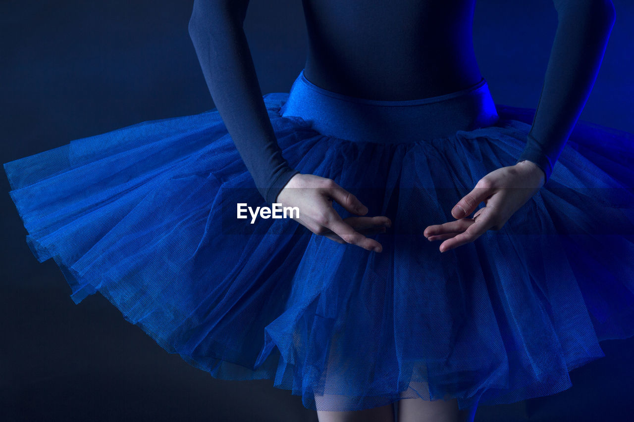 Midsection Of Dancer Standing Against Blue Background