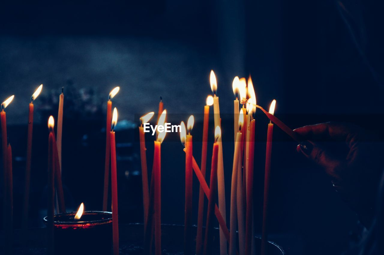 Close-Up Of Burning Candles In The Darkness