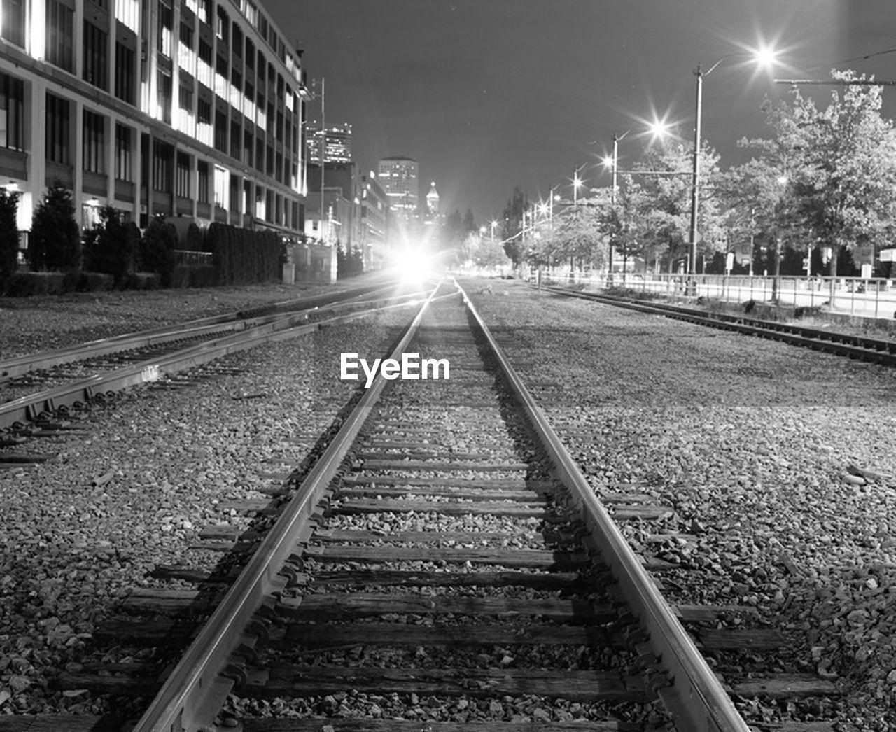 railroad track, rail transportation, night, transportation, illuminated, outdoors, street light, public transportation, the way forward, no people, building exterior, architecture, sky
