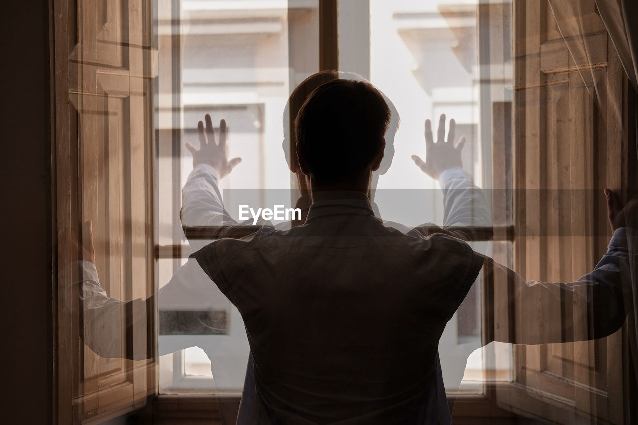 Double exposure of man looking through window at home