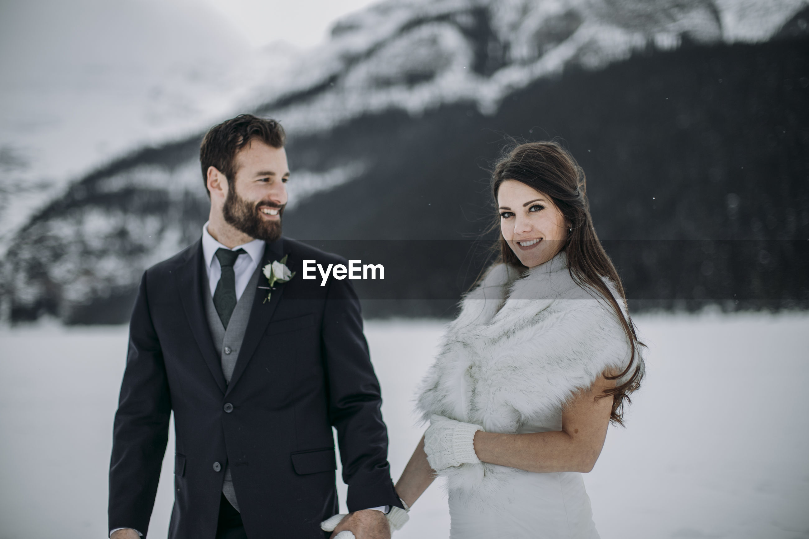 YOUNG COUPLE STANDING ON SNOW