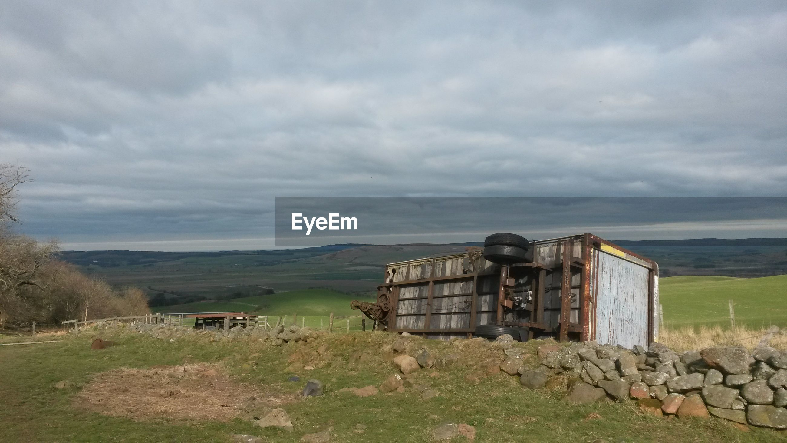 Abandoned trailer on field against cloudy sky
