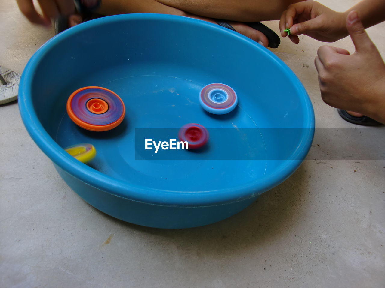 Cropped image of kids playing with spinning tops in plastic basket