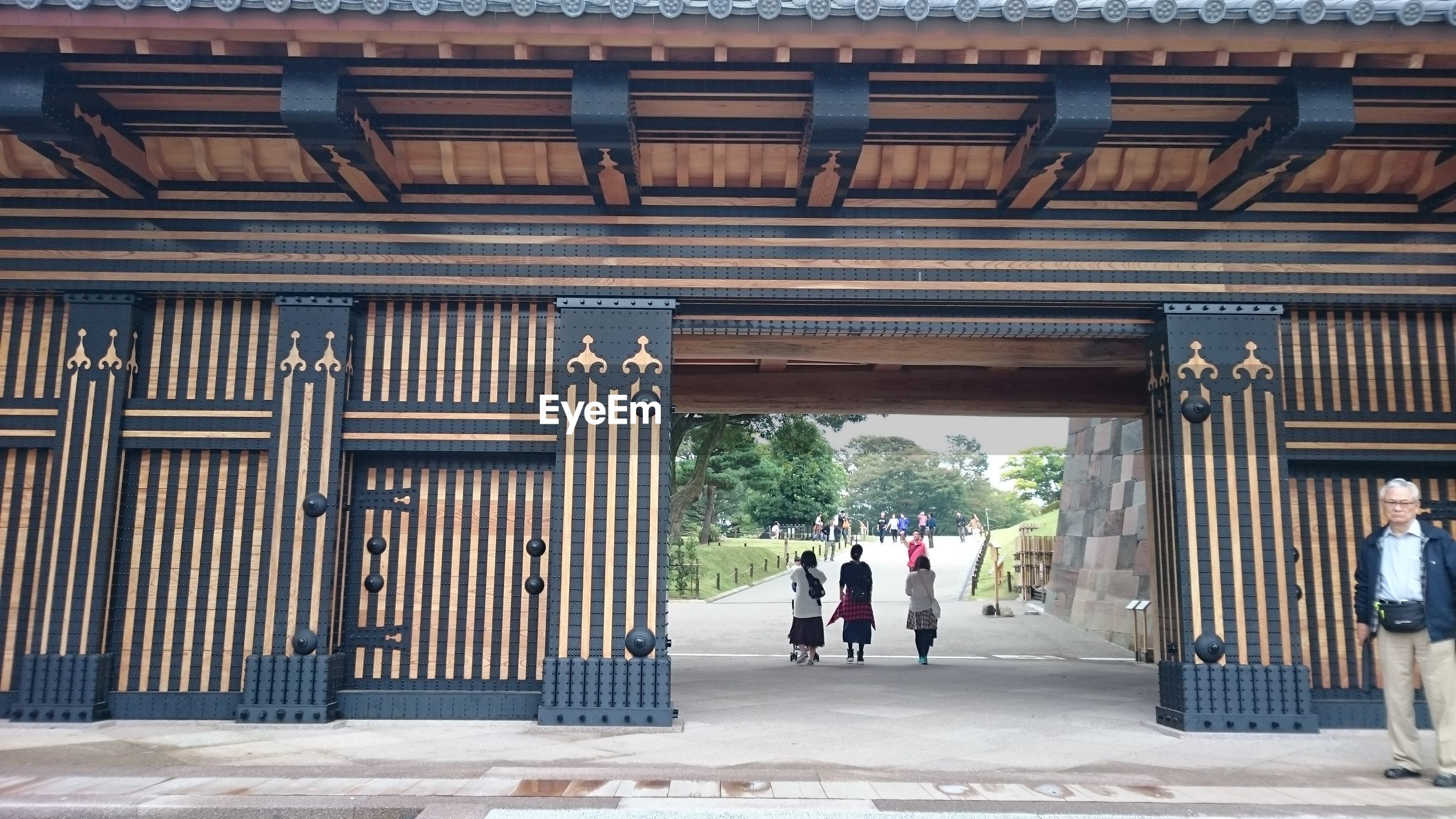 built structure, architecture, real people, building exterior, gate, day, men, architectural column, outdoors, full length, people