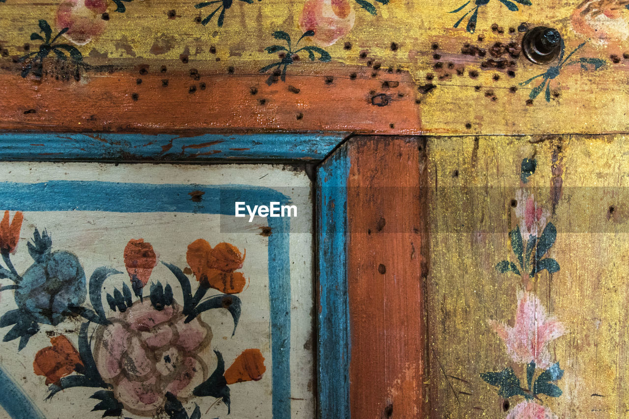 no people, wood - material, day, flowering plant, wall - building feature, full frame, old, weathered, flower, close-up, multi colored, architecture, indoors, pattern, built structure, door, plant, art and craft, entrance, blue, floral pattern