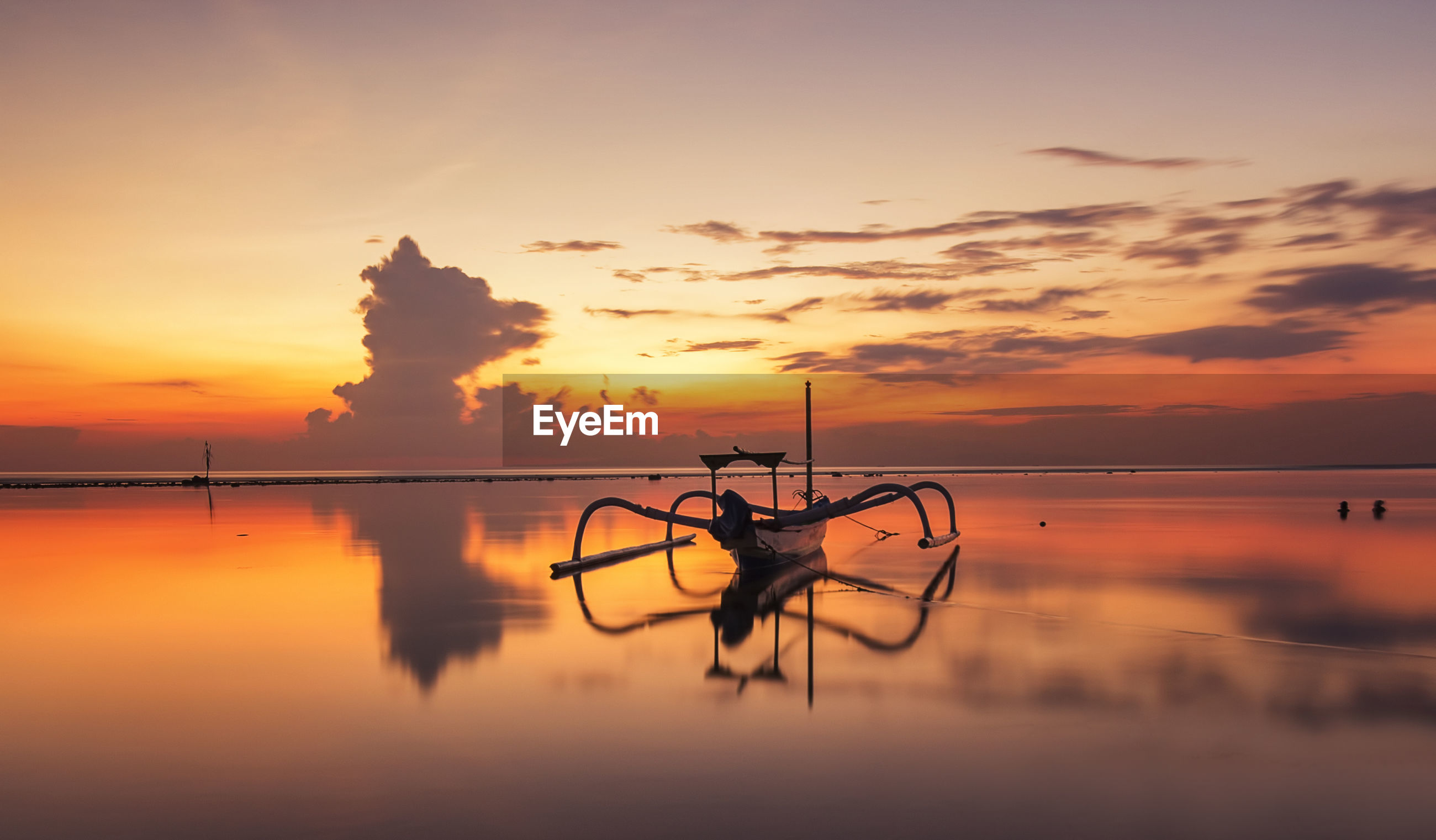 Jukung moored on shore against sky during sunrise