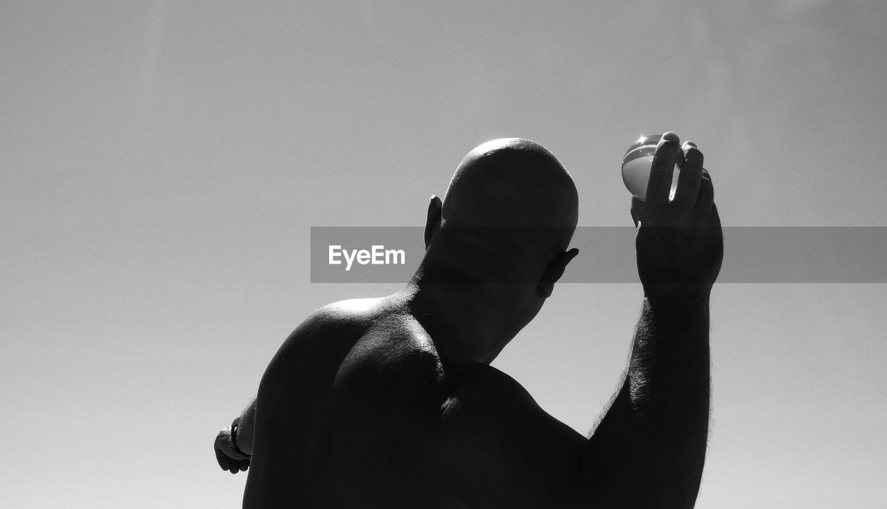 Rear view of bald man throwing crystal ball against clear sky