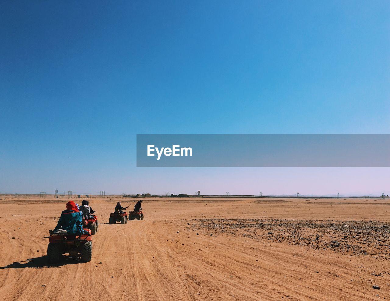 People On Buggies In Desert Against Clear Sky