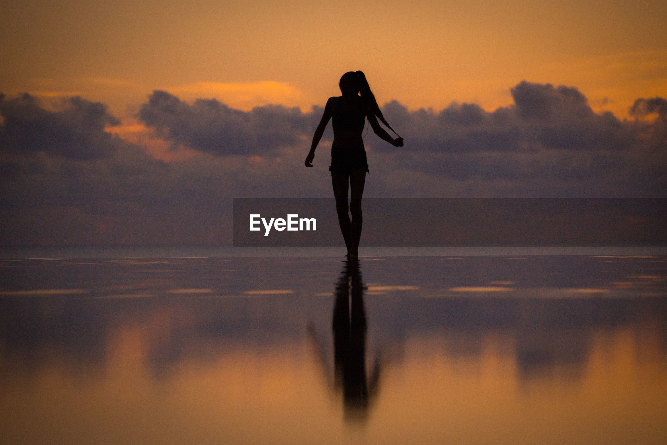Full length of woman doing ballet dancing in infinity pool by sea against sky
