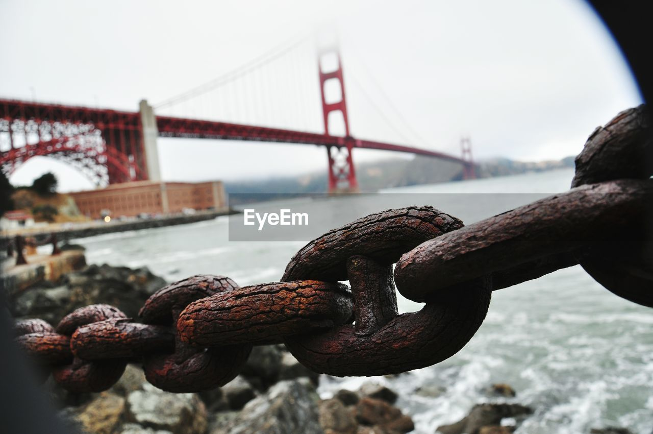 Close-up of rusty chain against golden gate bridge on san francisco bay