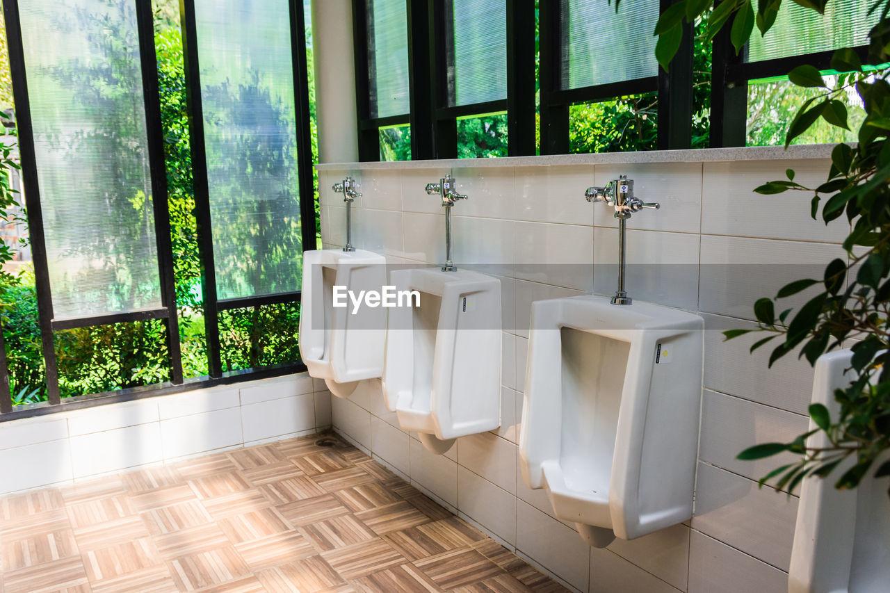 Close-up of urinals at public restroom