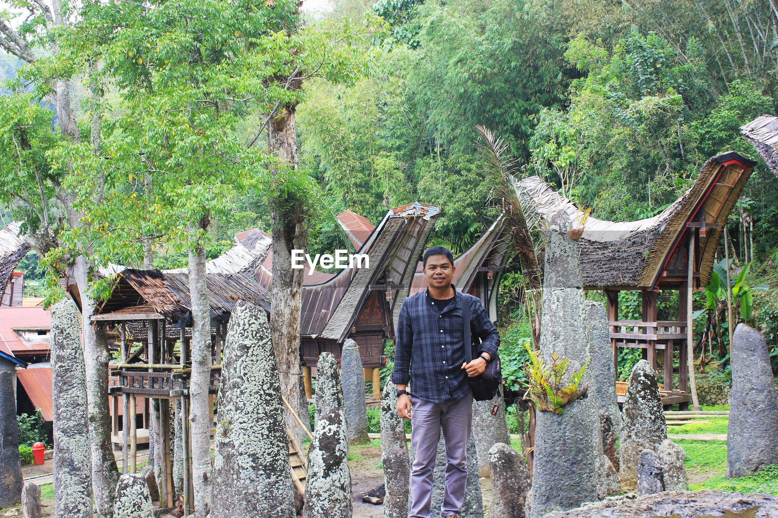 Portrait of man standing by traditional built structures against trees