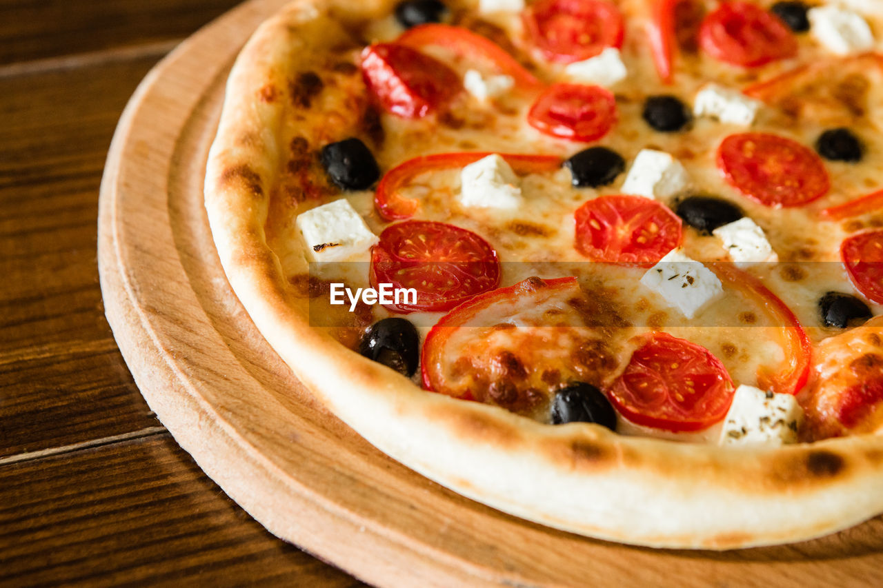 food and drink, food, pizza, fruit, freshness, dairy product, indoors, close-up, wood - material, cheese, no people, table, unhealthy eating, vegetable, tomato, olive, still life, italian food, selective focus, pepperoni, dieting