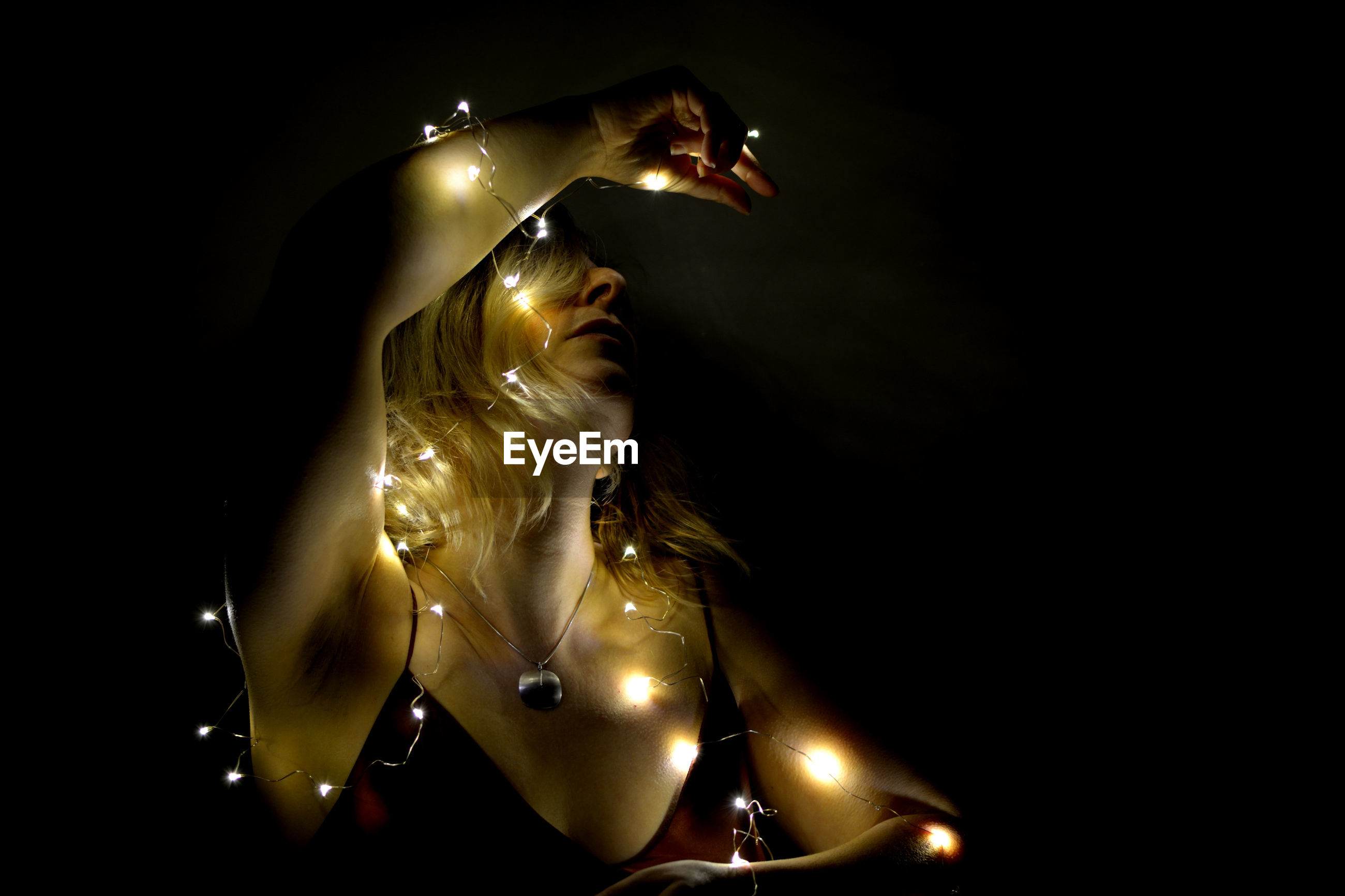 illuminated, indoors, studio shot, sculpture, no people, representation, human representation, lighting equipment, close-up, statue, low angle view, dark, copy space, gold colored, art and craft, black background, arts culture and entertainment, creativity, night