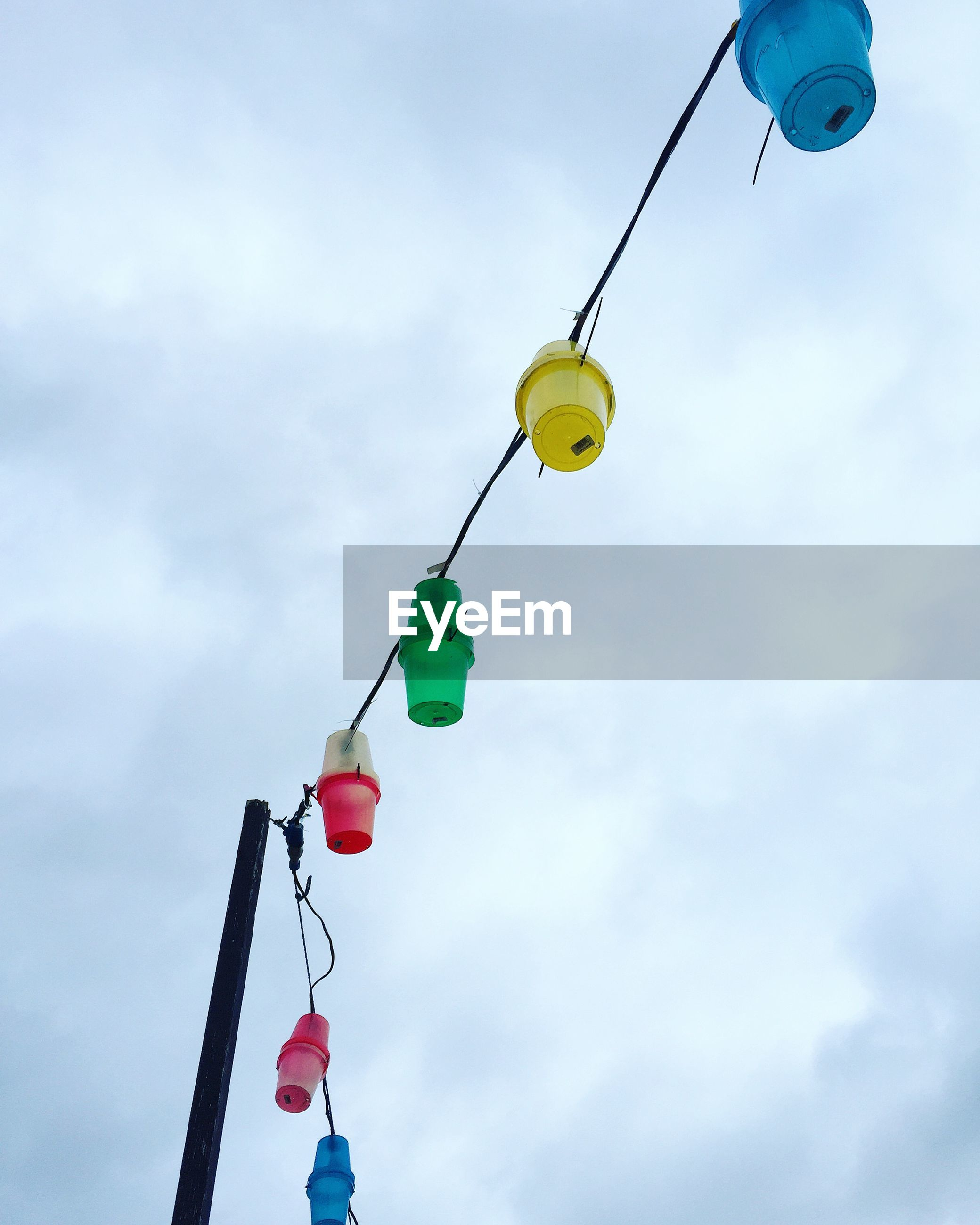 Low angle view of colorful lanterns against cloudy sky