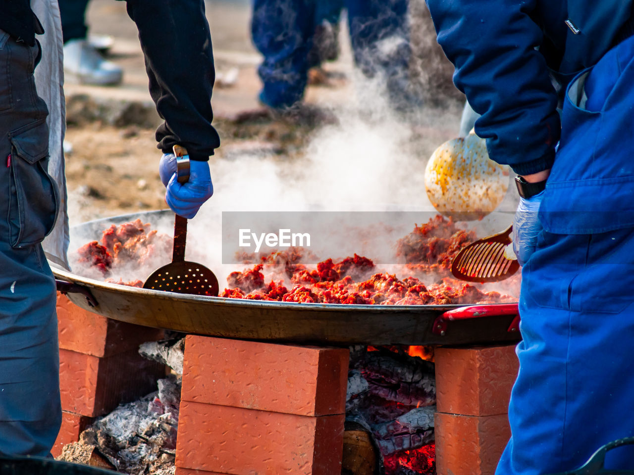 real people, food, smoke - physical structure, preparation, meat, food and drink, heat - temperature, freshness, barbecue, men, barbecue grill, standing, midsection, people, preparing food, two people, burning, incidental people, holding, day, hand, outdoors, street food