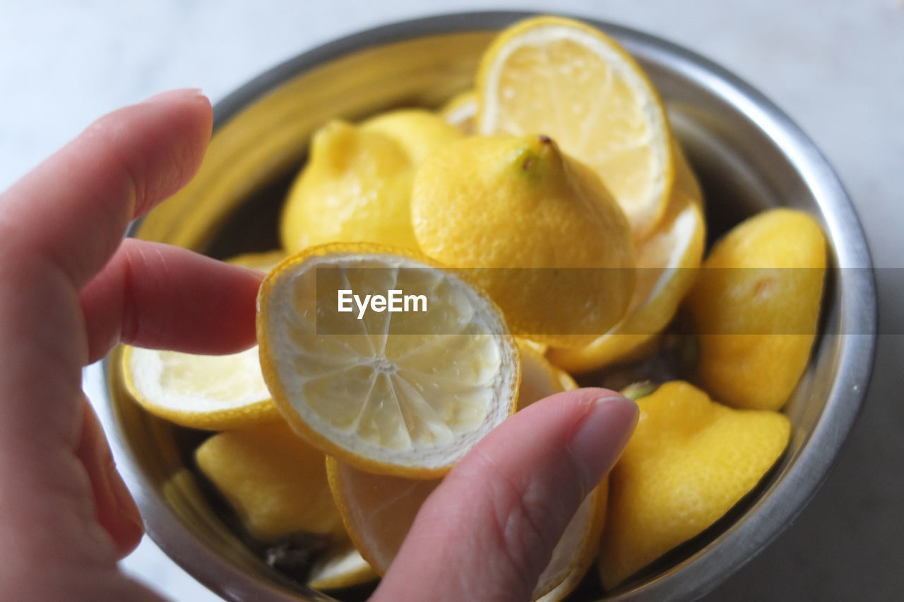 food, food and drink, fruit, healthy eating, citrus fruit, freshness, human hand, human body part, hand, lemon, wellbeing, one person, holding, indoors, slice, close-up, real people, yellow, finger, body part, orange