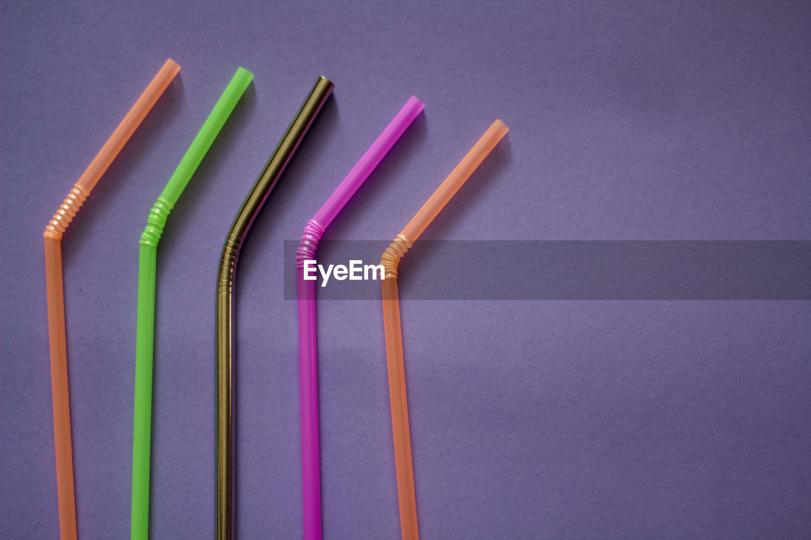 Close-up of colorful straws on purple background
