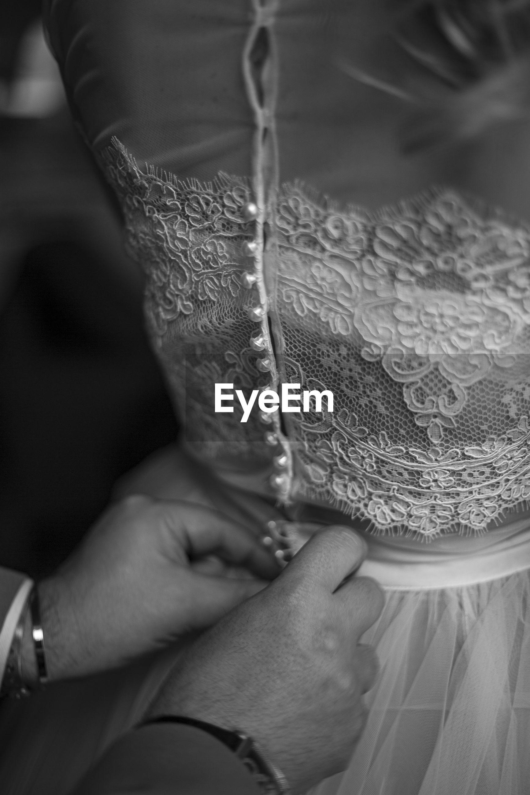 Close-up of hand dressing up bride