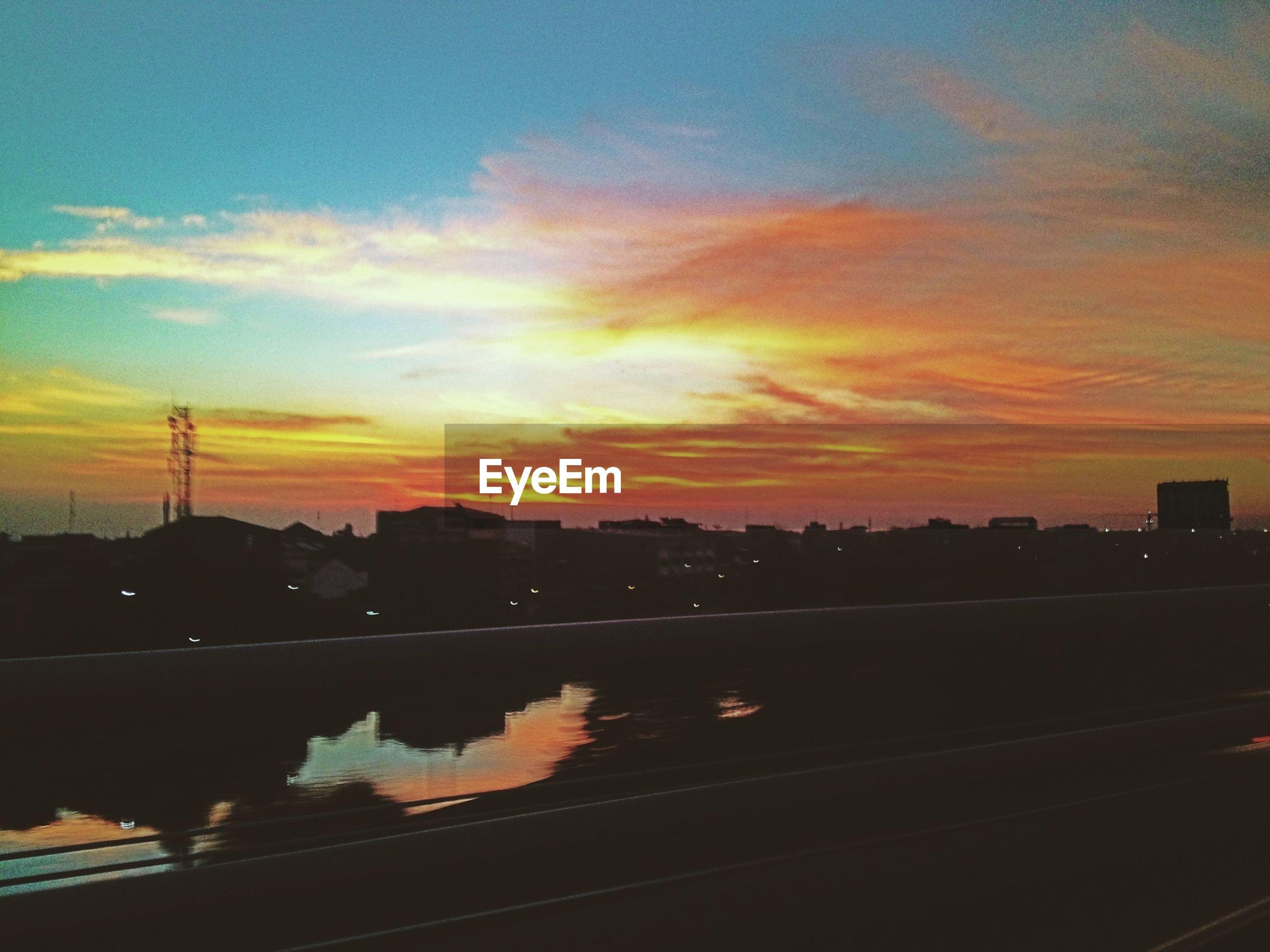 sunset, silhouette, orange color, sky, transportation, cloud - sky, city, building exterior, street light, railroad track, built structure, architecture, tree, car, road, dusk, nature, mode of transport, beauty in nature, scenics