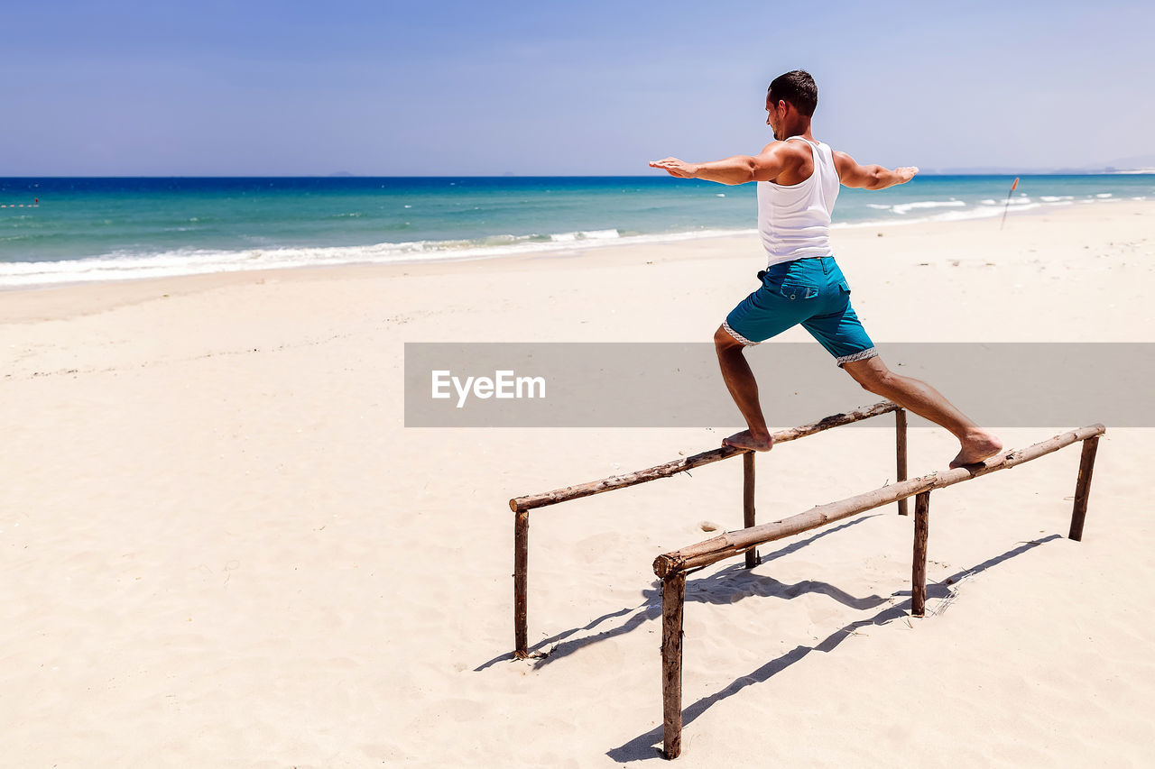 Side view of man balancing on beams on beach