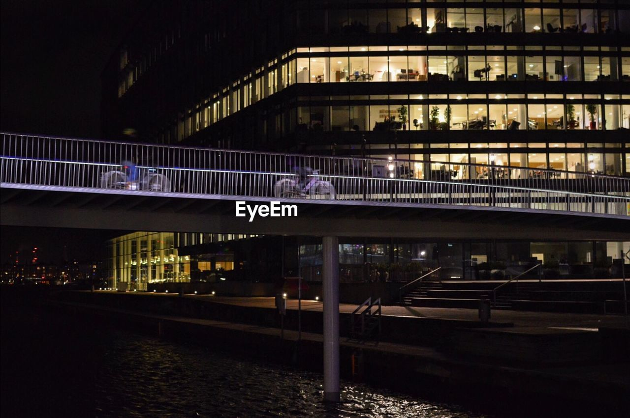 Bicycling on bridge against built structure at night