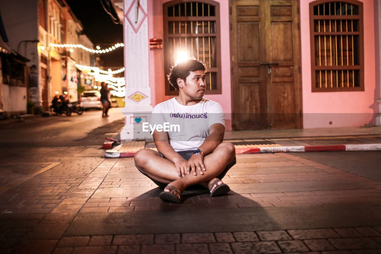 Young man looking away while sitting on footpath in city