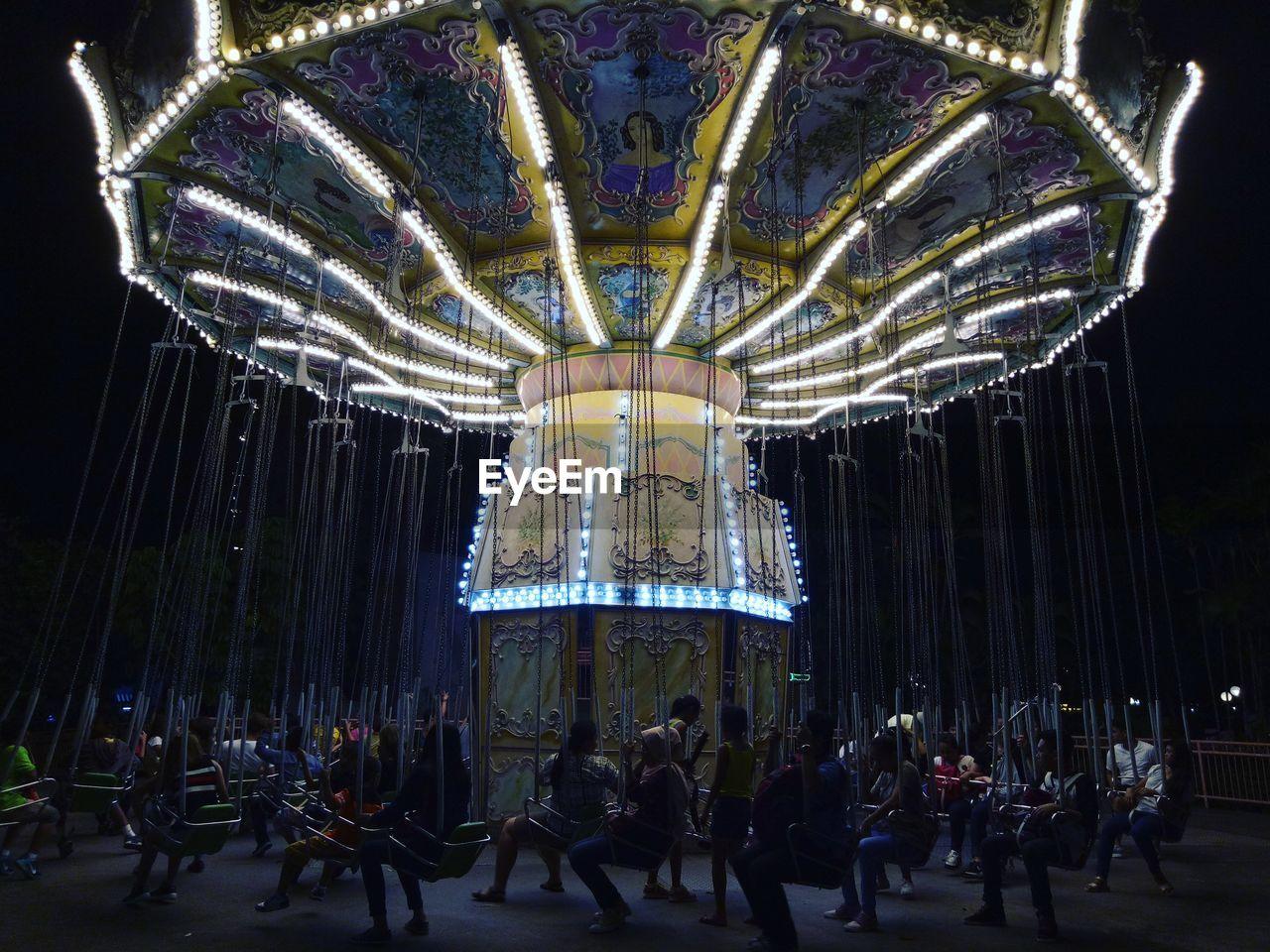 Illuminated chain swing ride in amusement park at night