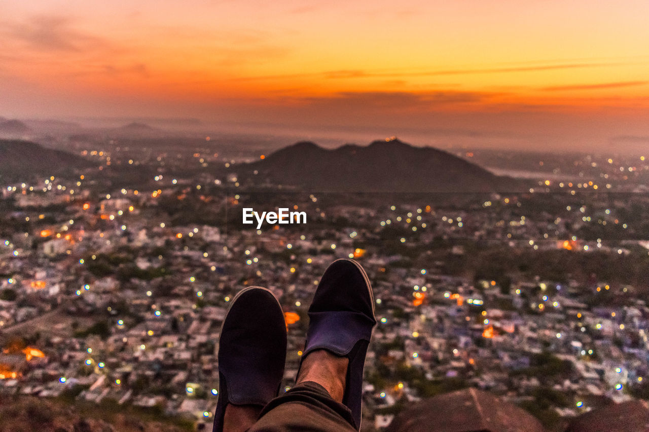 Low section of man looking at cityscape during sunset