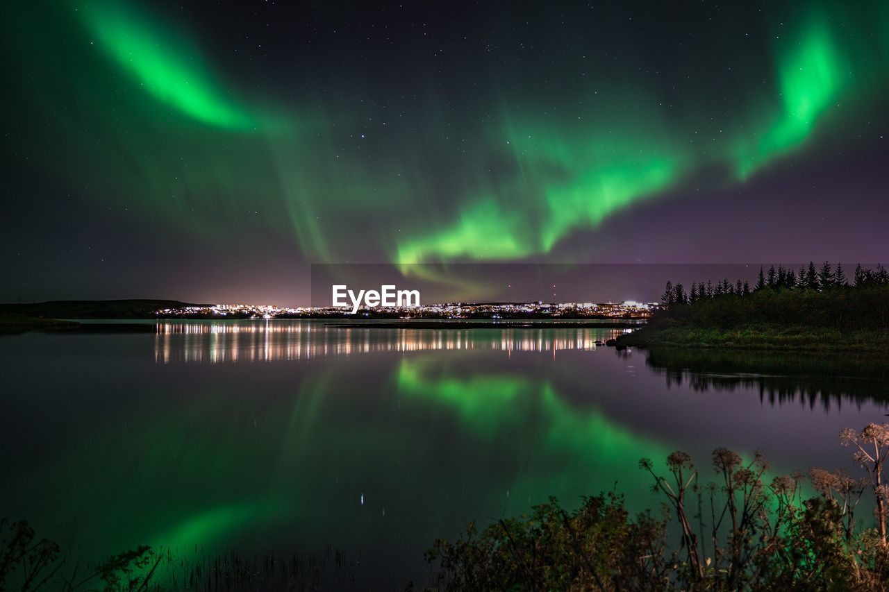 Scenic view of northern lights reflected on lake against sky at night