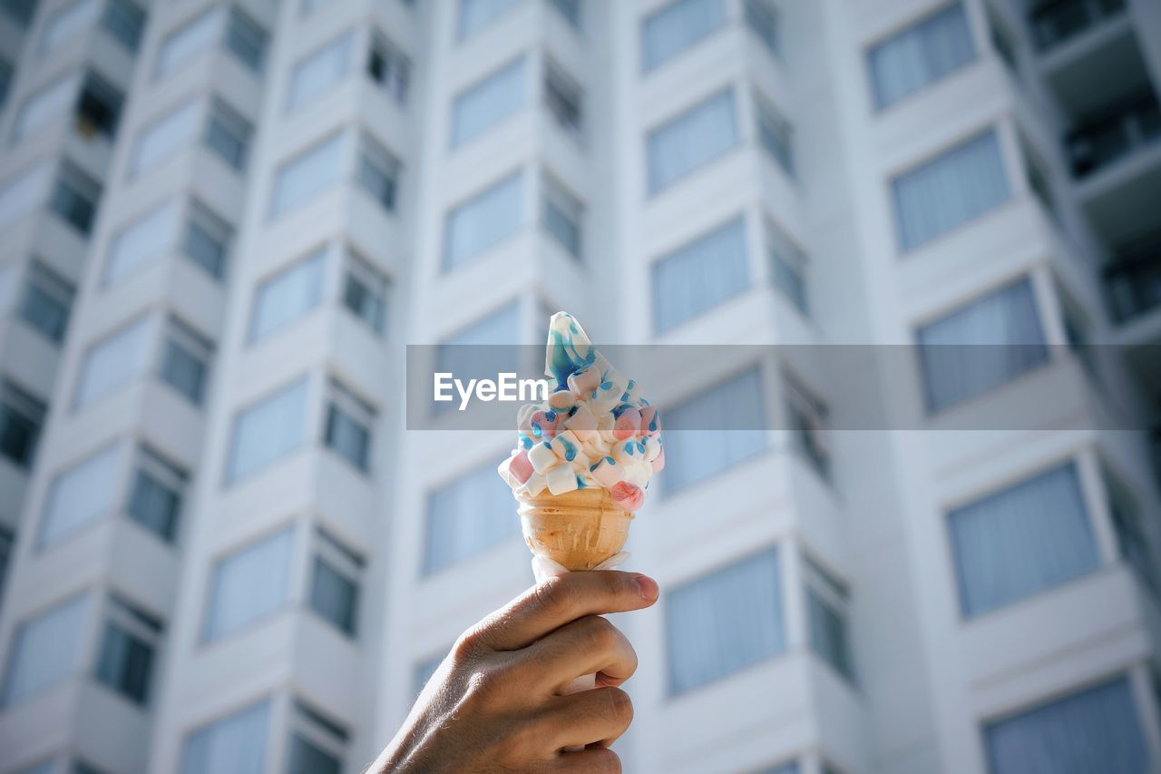 Hand holding ice cream cone against modern building