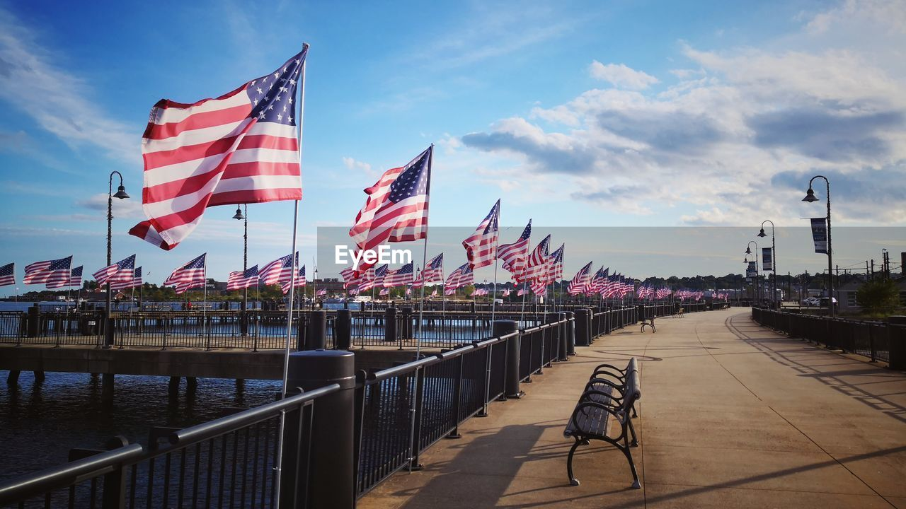 flag, patriotism, sky, architecture, built structure, cloud - sky, city, railing, nature, building exterior, water, striped, day, street, transportation, outdoors, no people, freedom, wind, independence, national icon
