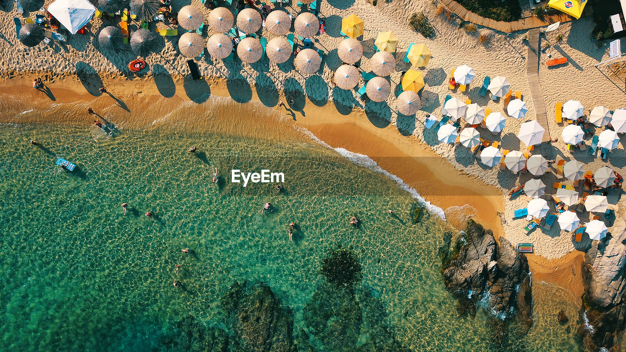 Aerial View Of People On Beach By Rock Formation