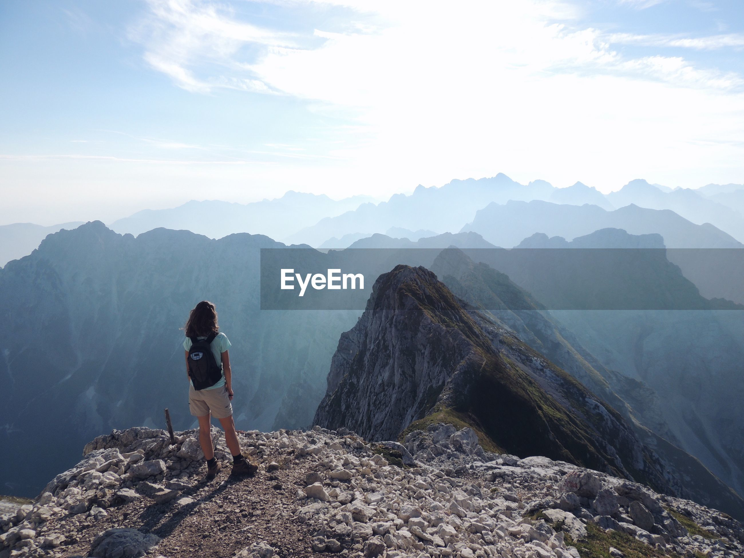 Rear view of young woman with backpack standing on mountain against sky