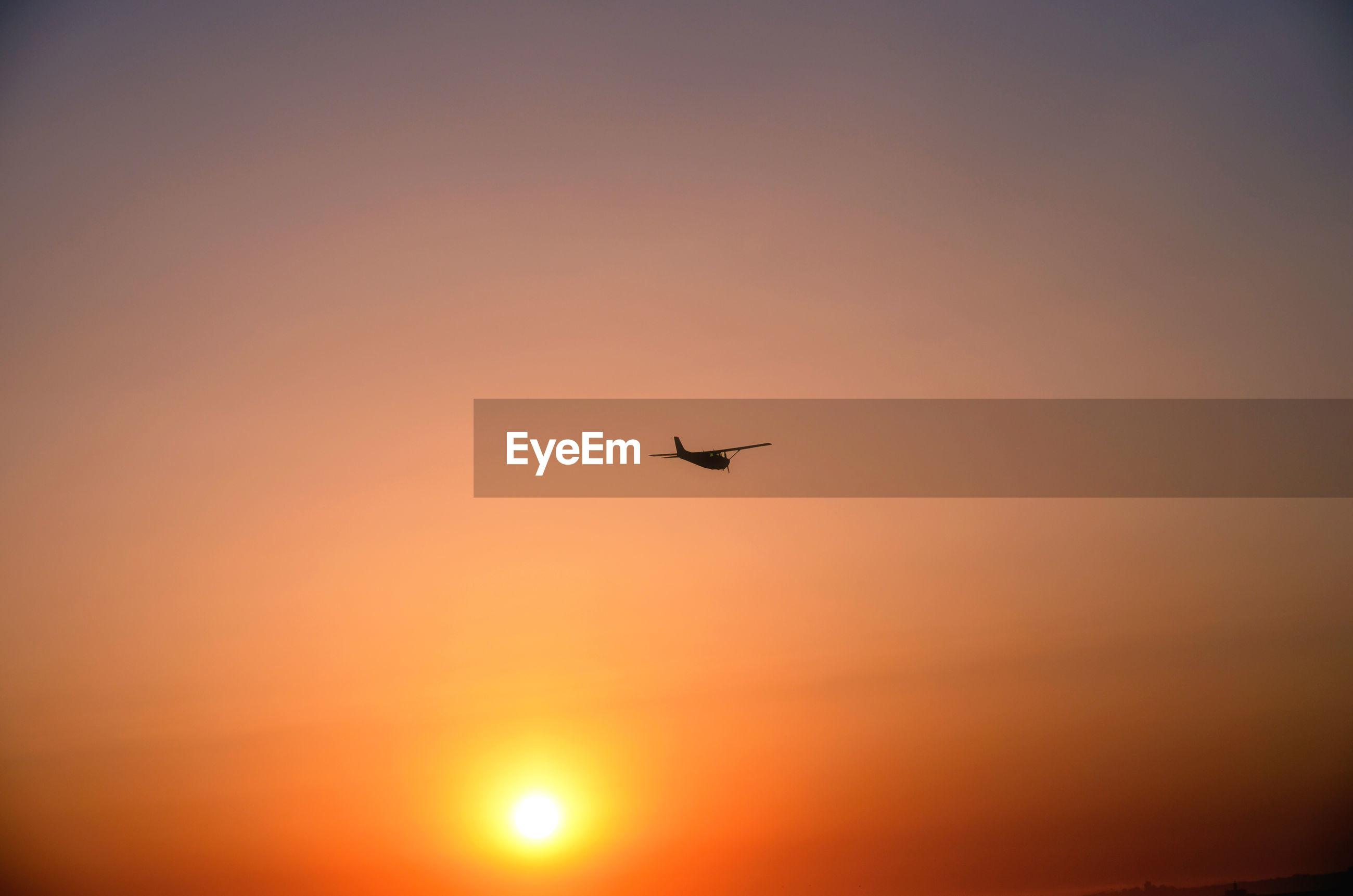 AIRPLANE FLYING AGAINST ORANGE SKY