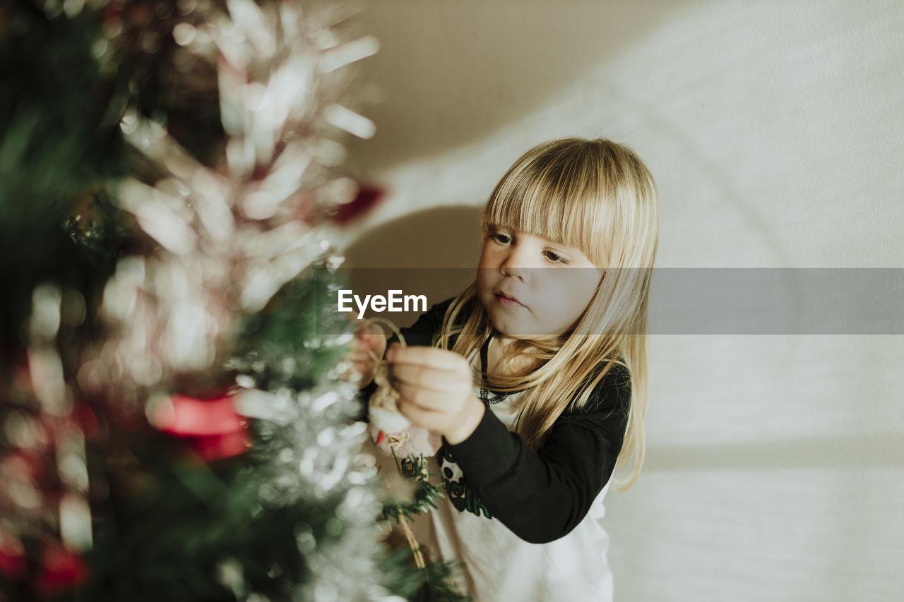 FULL LENGTH OF CUTE GIRL WITH CHRISTMAS LIGHTS