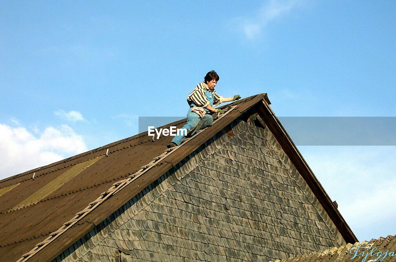 Low Angle View Of Man Climbing On House Roof Against Sky