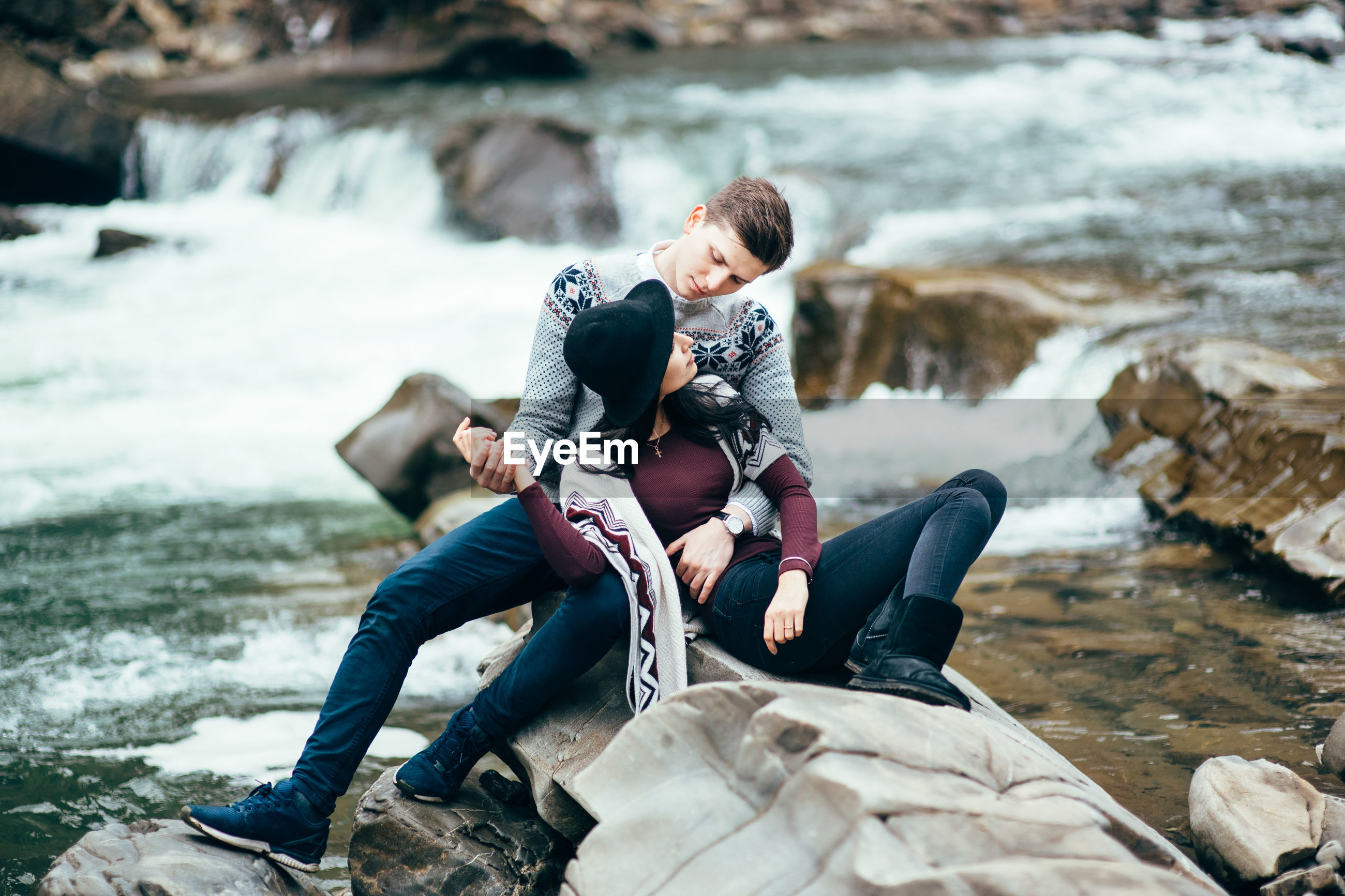PEOPLE SITTING ON ROCK BY WATER