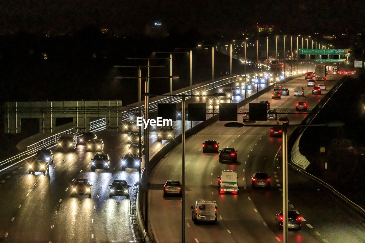 illuminated, transportation, night, motor vehicle, car, mode of transportation, road, city, land vehicle, motion, street, architecture, on the move, traffic, high angle view, built structure, no people, connection, highway, direction, outdoors, multiple lane highway