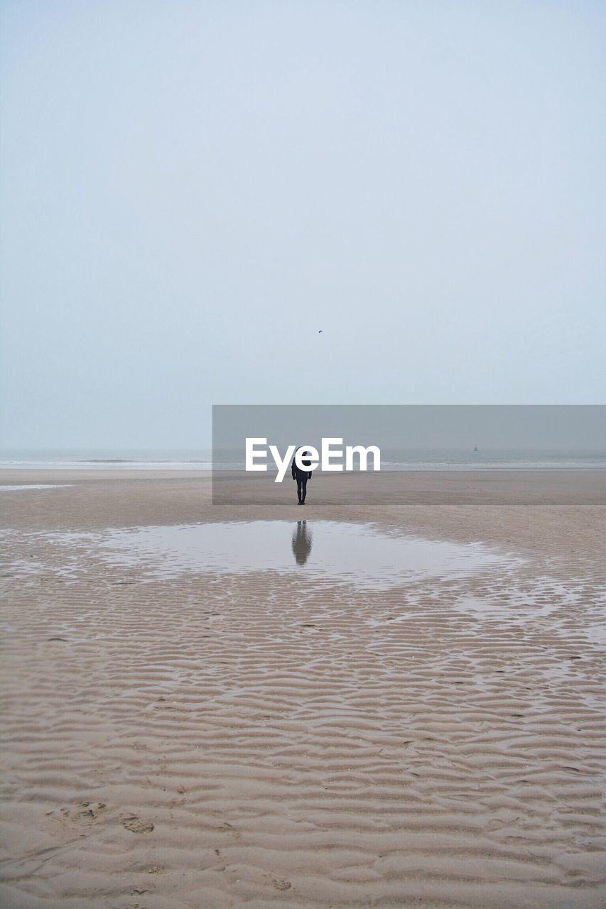 Full Length Of Man On Beach Against Clear Sky