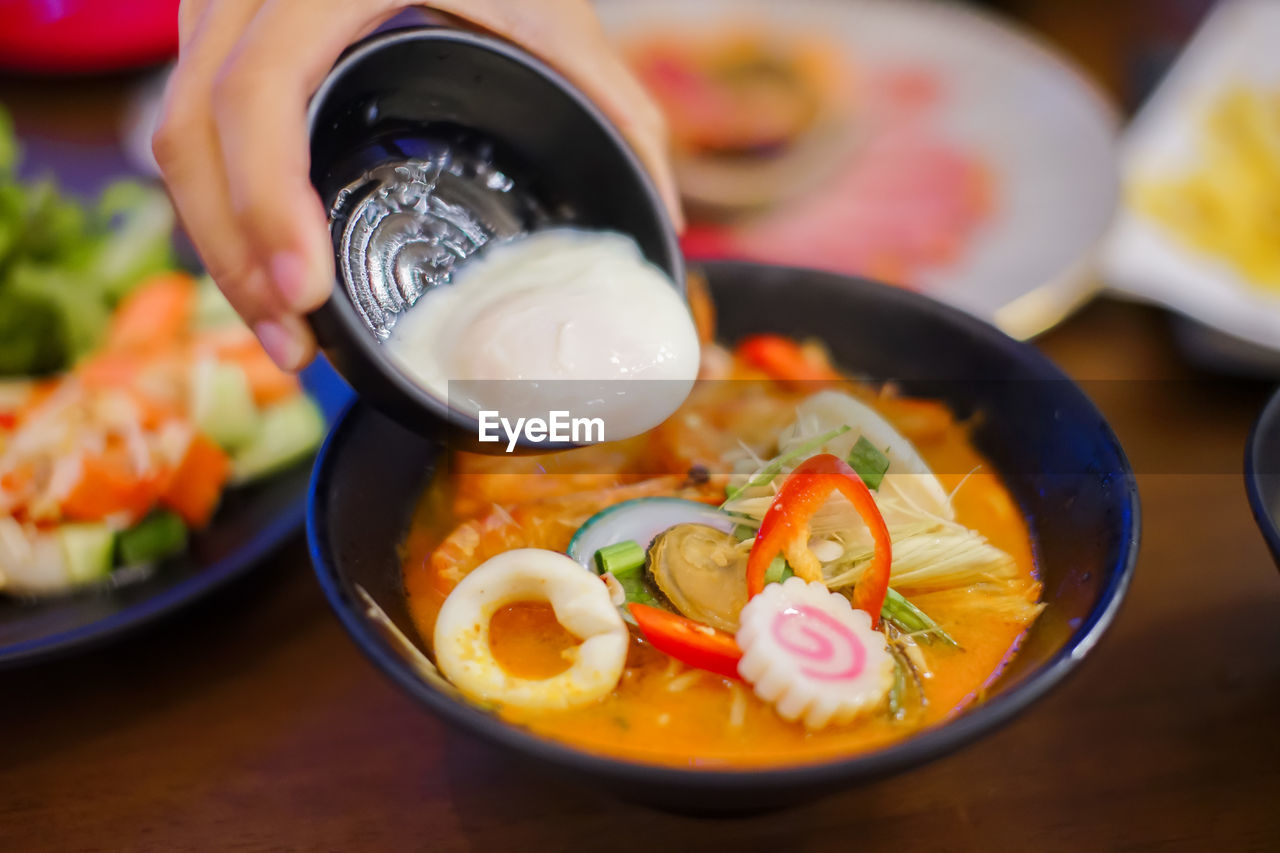 food and drink, food, healthy eating, bowl, ready-to-eat, table, freshness, indoors, wellbeing, asian food, close-up, serving size, one person, focus on foreground, selective focus, human hand, japanese food, still life, hand, korean food