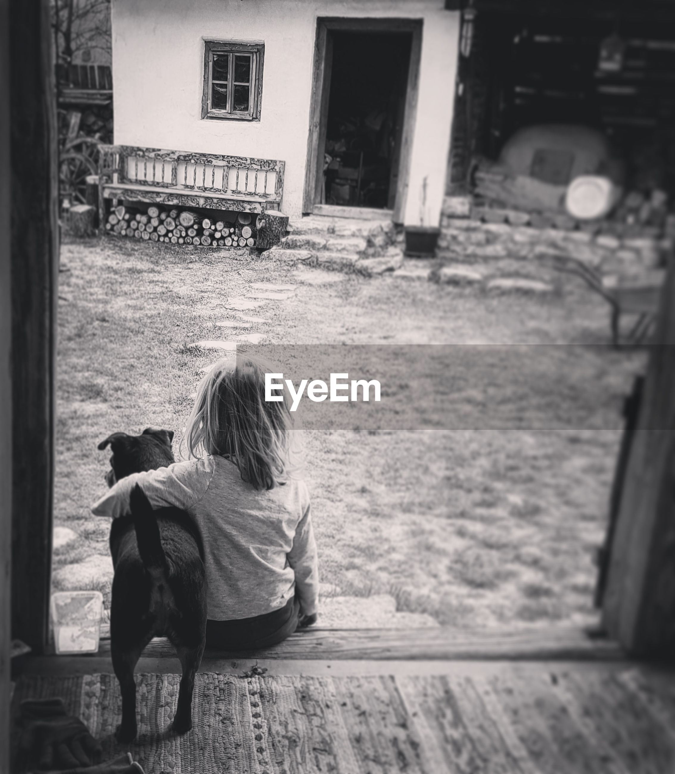 Rear view of girl with dog sitting at porch