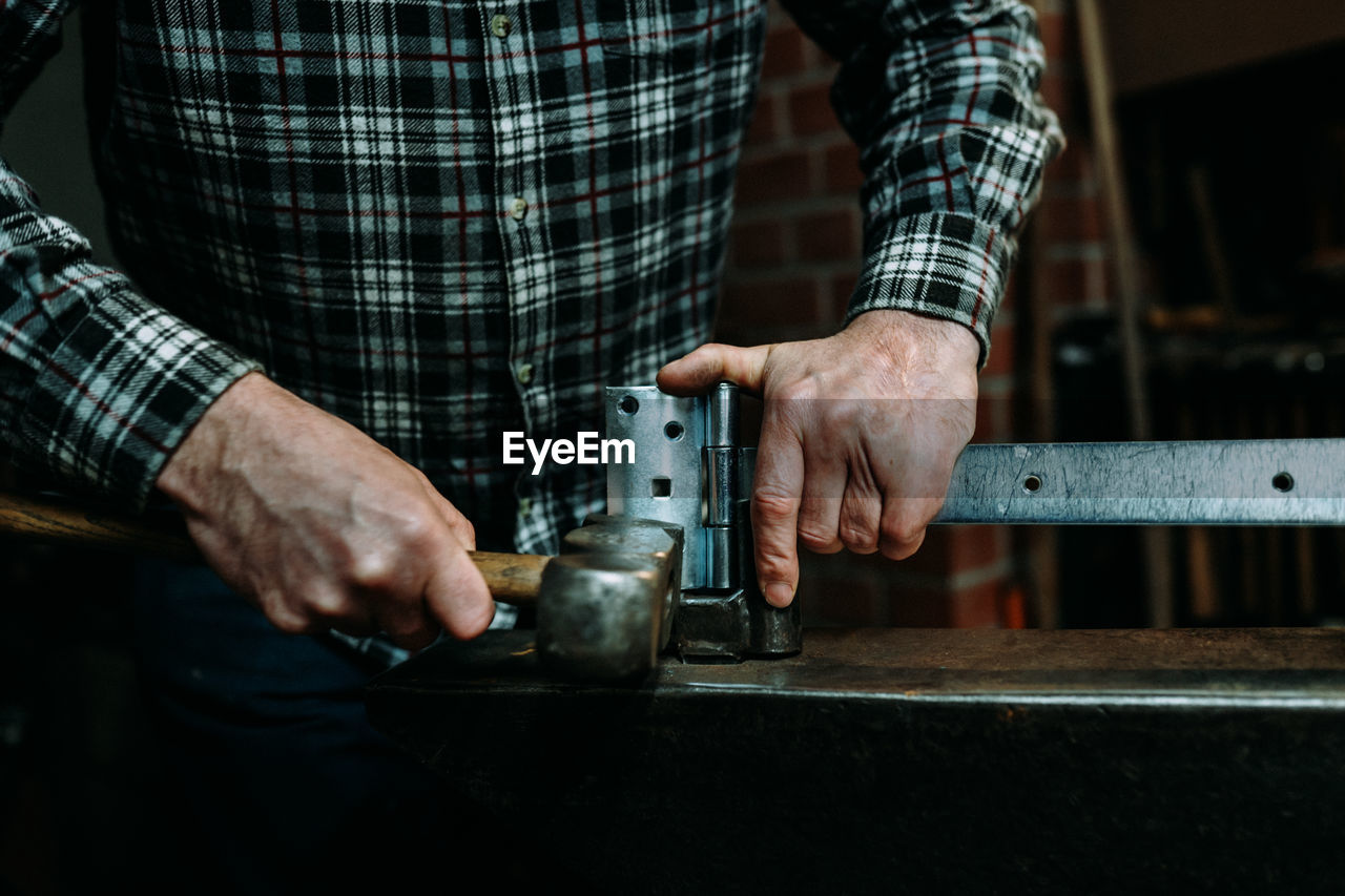 Midsection of man hammering latch in workshop
