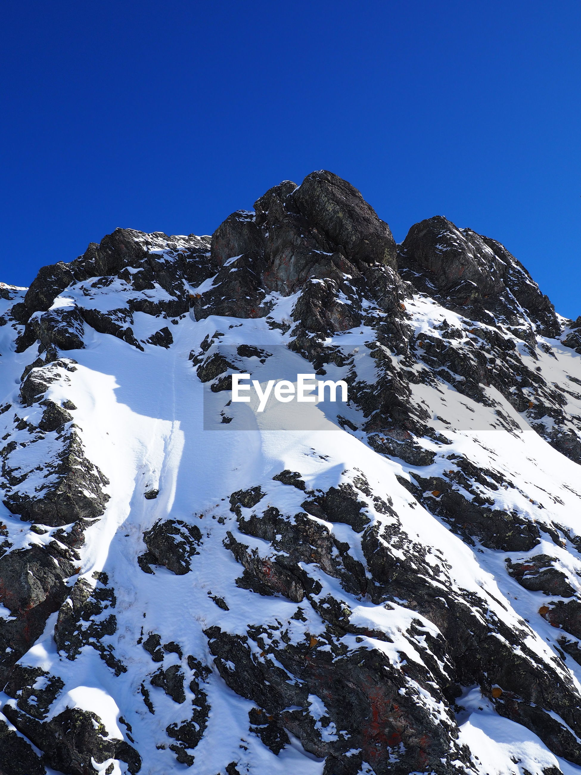 Idyllic view of snowcapped mountain against clear blue sky